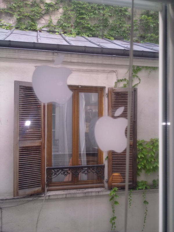 Apple stickers stuck to the window of an appartment.